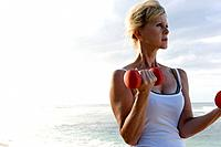 Senior woman lifting dumbbells on beach, copy space