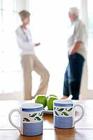 Senior couple standing at the door to terrace, mugs and apples on table in foreground, differential focus