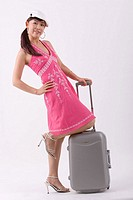 Portrait of young woman smiling, holding suitcase
