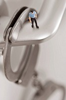 Figurine of man standing on door handle with handcuff hanging, close_up