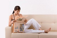 Young woman sitting on sofa reading newspaper