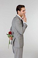 Businessman holding rose behind back
