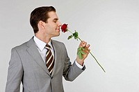 Businessman holding rose, close_up