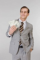 Young businessman holding currency, close_up