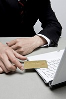 Busineesperson holding credit card on laptop