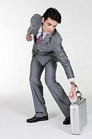 Businessman picking up a briefcase