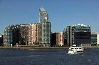 Sightseeing boat passing office towers at Canary Wharf, London,UK