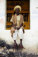A man in clogs sitting in a window in Kumbhalgarh, Rajasthan, India