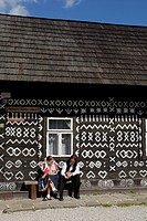 Young man and woman dressed in traditional folk costume outside cottage, Cicman, Slovakia