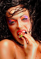 painted woman _ a little bit crazy _ eating a strawberry