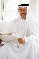 Man sitting indoors with newspaper smiling high key/selective focus