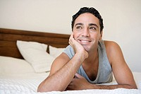 Man relaxing on bed in bedroom smiling selective focus