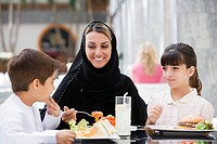 Woman and two young children at restaurant eating and smiling selective focus