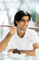 Man at restaurant eating dessert and smiling selective focus