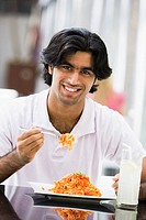 Man at restaurant eating spaghetti and smiling selective focus