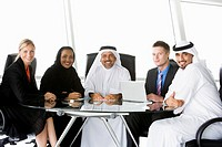 Five businesspeople in office with laptop smiling high key/selective focus