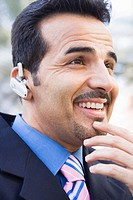 Businessman outdoors wearing headset and smiling selective focus