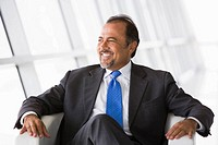 Businessman sitting indoors looking out window smiling high key/selective focus