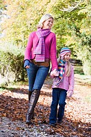 Woman and young girl walking outdoors in park and smiling