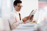 Businessman Reading a Newspaper in a Restaurant