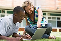 Two students outdoors on lawn with laptop