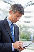 Businessman outdoors using personal digital assistant