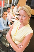 Businesswoman with four businesspeople at boardroom table in background