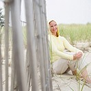 Mid adult woman sitting near a fence and smiling