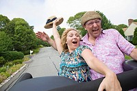 Close_up of a mature couple standing on a jeep and shouting