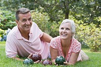 Mature couple lying on grass and holding bocce balls