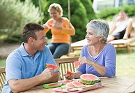 Mature couple eating watermelon slice