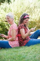 Side profile of two mature women sitting back to back in a park and listening to MP3 players