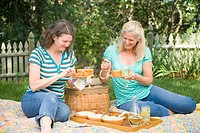 Two mature women having picnic in a park