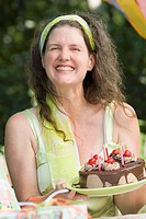 Mature woman holding a birthday cake and smiling