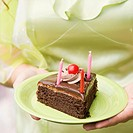 Mid section view of a woman holding a plate of birthday cake slice