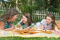 Mature woman with her two daughters having picnic