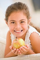 Young girl eating apple in living room smiling