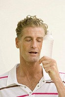 Close_up of a mature man holding a water bottle with his eyes closed