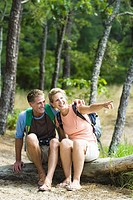 Mature couple sitting on a tree trunk in a forest and pointing