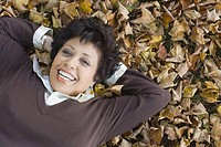 Portrait of a mature woman lying on fallen leaves and smiling