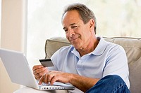 Man in living room with laptop and credit card smiling