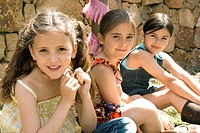 Three young girls sitting outdoors