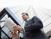 Businessman reading newspaper outside office building low angle view