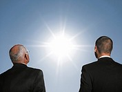 Businessmen looking at the sun head and shoulders back view