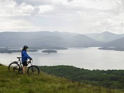 Woman on bicycle near lake