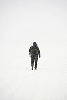 Person walking on snow, rear view