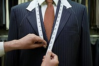 Tailor measuring business man for suit mid section close up