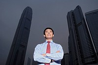 China Hong Kong business man standing in front of International Finance Centre building low angle view portrait