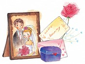 A picture frame of a bride and groom next to a gift box, flowers and anniversary card