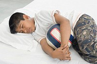 High angle view of a boy sleeping on the bed and holding a football